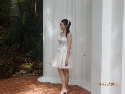 A bride-to-be makes a practical selection of a short wedding dress for the warm climate of Singapore.
